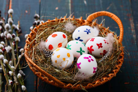 straw twig: Easter eggs in basket and willow branches on wooden table. Rustic