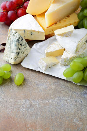 different types of cheese: Different types of cheese with grapes on slate. Delicatessen Stock Photo
