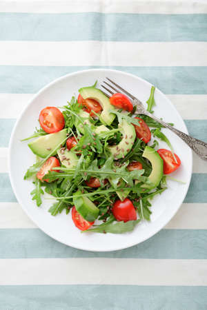 stripy: Green Avocado Salad with cherry tomatoes and arugula on a stripy background. Top view