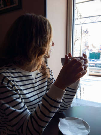 coffeetime: Young woman with coffee cup in hand sitting near the window at a table in cafe Stock Photo