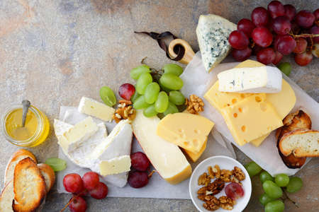 Different types of fresh Cheeses with grapes, honey, bread and walnuts on the slate background. Top view