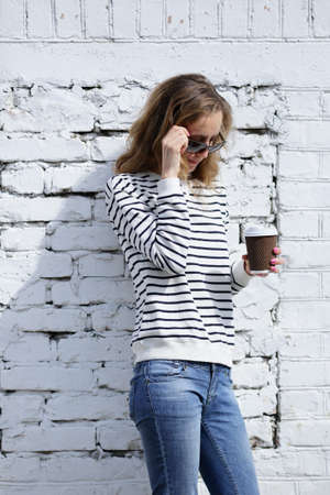 cofee cup: Beautiful woman in sunglasses with a disposable cofee cup on the background old brick wall