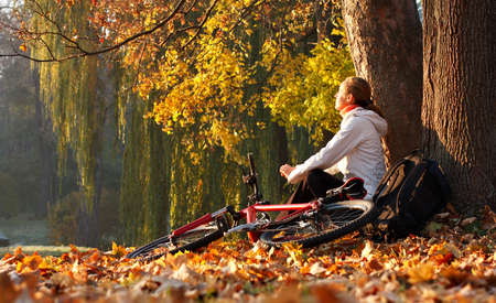 Relaxing woman cyclist with bike sits among fallen leaves in autumn nature illuminated by the bright rays of the rising sun and enjoy recreation photo