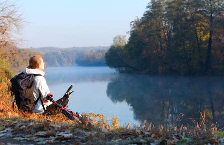 Woman cyclist sitting on the riverside enjoying the recreation. Autumn outdoor photo