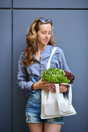 linen bag: Young stylish woman is holding in their hands a linen Bag with Lettuce Salad against the background of a gray wall