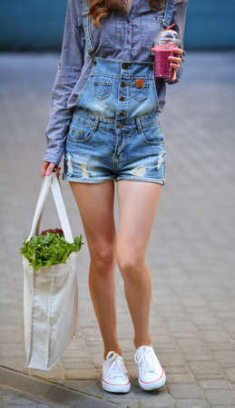 linen bag: Linen Bag with Lettuce Salad and Smoothies in disposable cup in the hands of sexy woman hipster Stock Photo