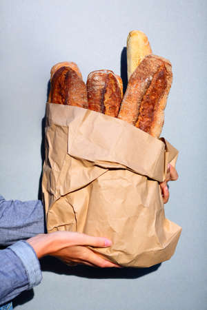 French baguette. Paper bag with baguettes in hands of woman closeup against the gray background Stock Photo