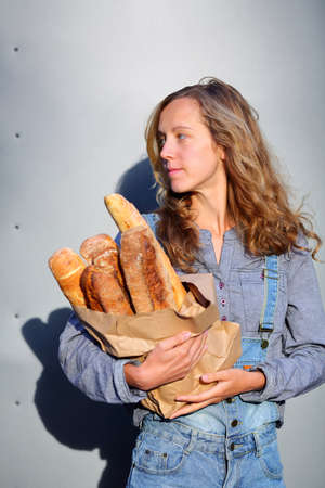 clothed: Stylish blonde woman clothed in jeans overalls and a shirt is holding in their hands a paper bag with fresh baguettes