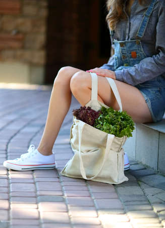 linen bag: Lettuce. Linen bag full of fresh salad stands on paving stone near the legs of stylish woman. Street outdoors Stock Photo