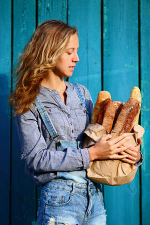 crust crusty: French baguette. Blonde woman is holding in their hands a paper bag with baguettes against the old wooden boards