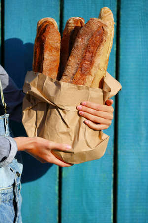 artisan bakery: Baguettes. Paper bag with baguette in hands of woman against the wooden fence Stock Photo