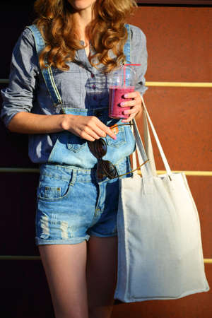 linen bag: Woman Hipster with Smoothies in disposable cup, Linen Bag and sunglasses keep in their hands against the background of brown striped wall