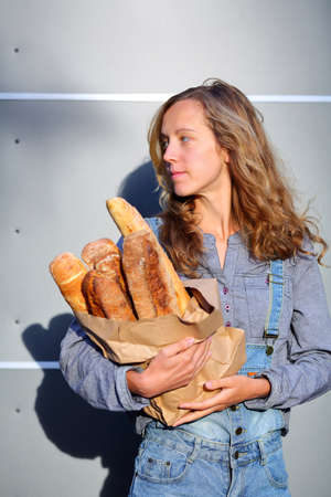 clothed: Blonde woman clothed in jeans overalls and a shirt is holding in their hands a paper bag with fresh french baguettes Stock Photo