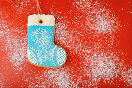 botas de navidad: Christmas cookies in the shape of boots strewn with snow on red background Foto de archivo