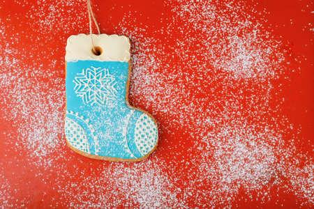 botas de navidad: galletas de Navidad en la forma de botas llenas de nieve sobre fondo rojo