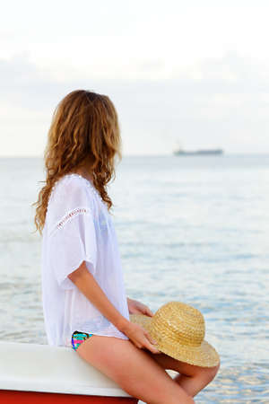 mujer mirando el horizonte: Young woman on the beach looking at the silhouette of the ship on the horizon. Summer vacations concept