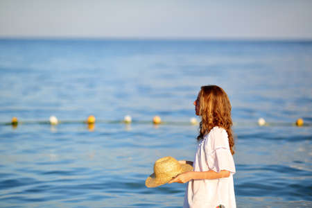 Young long haired woman in white tunic and straw hat in hands on the beach. Summer vacations concept