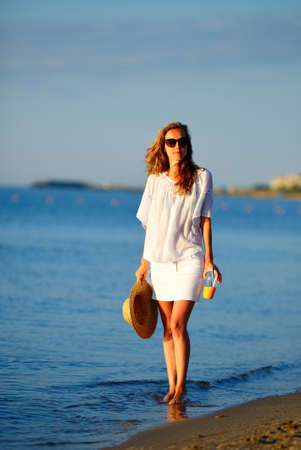 Young woman in sunglasses with orange juice and hat in hand in white clothes on the beach. Summer vacations concept