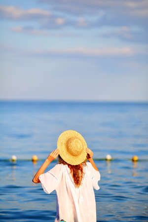Woman in hat and white dress in sea water on the beach back to us. Summer vacations concept