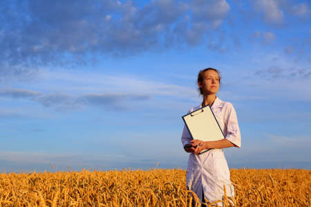 Agronomist or a student or a scientist with document in hand against the background of a golden wheat field and a blue sky. Agricultural business Stock Photo