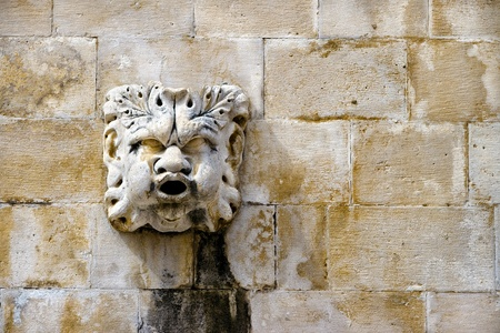 sculpted: Sculpted stone mask figure on ancient fountain on the side of Church of Saint Blaise  St Vlaha  Dubrovnik, Croatia Stock Photo