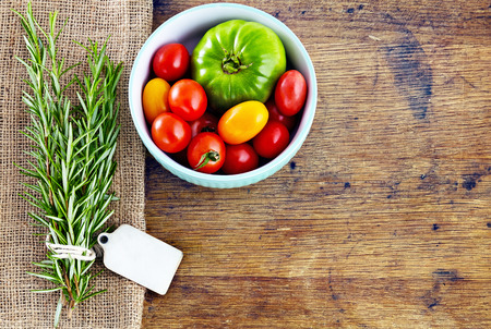 Fresh rosemary with tag, red and green tomatoes on rustic wooden table  photo