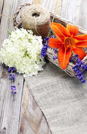 Bunch of lavender flowers and lily in basket  on an old wood table photo