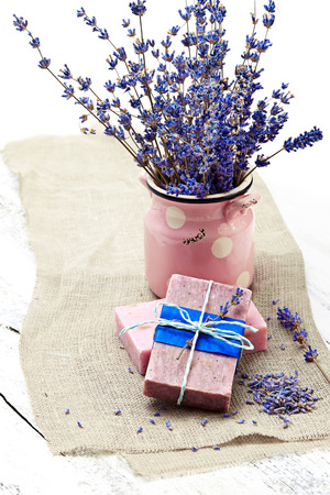 Bunch of lavender flowers,soap  on old wooden background.Spa treatment. photo