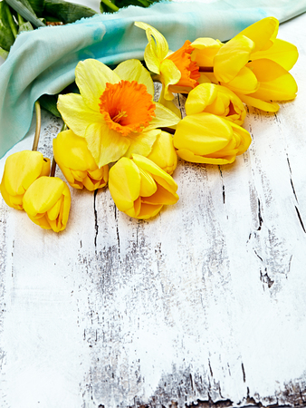 Bouquet of yellow narcissus and tulips on white wooden background