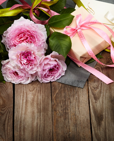 pink roses bouquet and gift box on a wooden background Imagens