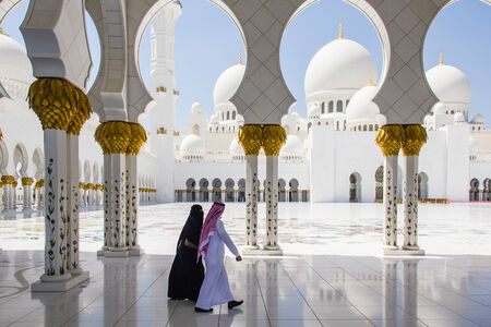 worshipers: ABU DHABI - MARCH 31, 2013  A muslim man and woman walking at Sheikh Zayed Grand Mosque taken on March 31, 2013 in Abu Dhabi, United Arab Emirates