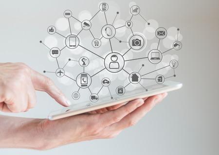 Internet der Dinge Konzept IoT mit männlichen Händen halten Tablette oder große Smartphone, um verschiedene Geräte und intelligente Maschinen zu verbinden.