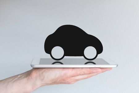 disruption: Digital mobility and mobile computing concept. Black car icon as Example for disruptive transportation and taxi services. Hand holding modern smart phone or tablet white.