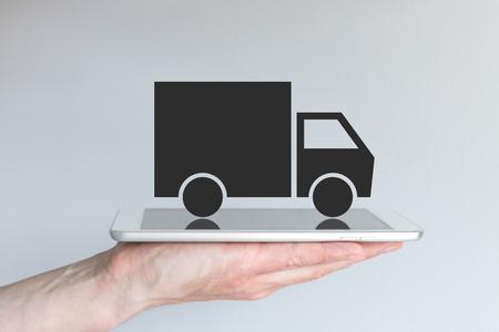 ref: Concepto de disruptivo modelo de negocio de la logística de transporte digitales. Mano que sostiene la tableta o teléfono inteligente grande delante de fondo gris. Símbolo de un camión negro simplificado.