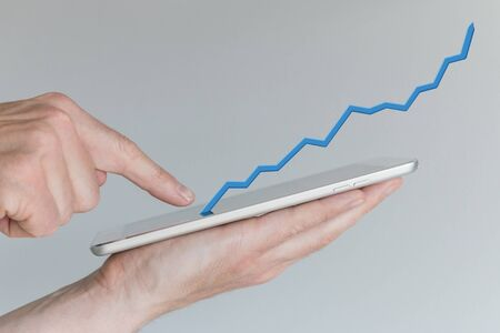 sales growth: Hand holding tablet. Concept of Increasing sales from mobile online shopping. Positive growth chart from use of smartphones tablets.