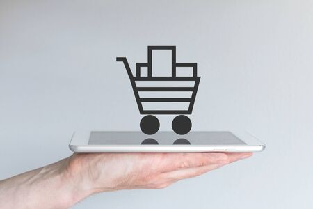 sale icon: Concept of mobile online shopping. Hand holding tablet or large smart phone in front of gray background. Shopping cart icon with reflections on smart phone.