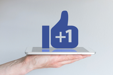Social network thumbs up icon with plus sign. Concept of mobile computing and social media. Hand holding tablet or smart phone.
