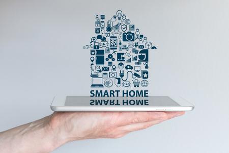 Smart Home-Automation-Konzept. Hintergrund mit Hand halten Smartphone und schwimmende Text und Symbole. Reflexionen auf dem Bildschirm.