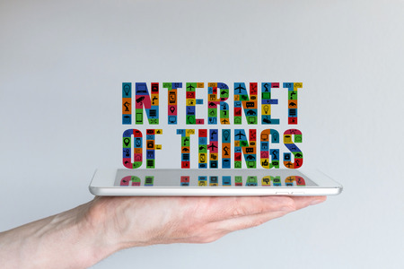 reflection internet: Internet of Things IoT concept. Background with hand holding tablet and floating text in different colors and with symbols. Reflections on screen. Stock Photo