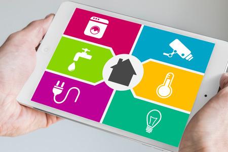 Domotique intelligente et le concept de l'informatique mobile. Mains tenant comprimé blanc et argent moderne avec écran domotique du tableau de bord.