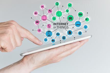 Internet van alles IOT concept. Kleurrijke pictogrammen van de aangesloten apparaten binnen een draadloos netwerk van objecten. Hand holding tablet met de vinger aanraken van het scherm. Stockfoto