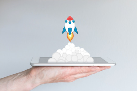eg: Concept of successful mobile computing business or strategy, eg for app development or business startups. Rocket launching from white and silver tablet or smart phone. Hand holding mobile device.