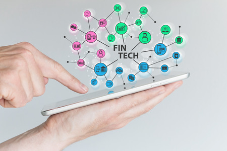 hand holding: Fin Tech and mobile computing concept. Hand holding tablet with network of financial information technology objects in front of gray background.