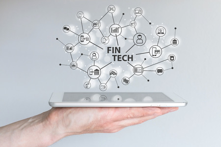 Fin Tech and mobile computing concept. Hand holding tablet in front of gray background with Connected finance, sales, marketing and payment information.