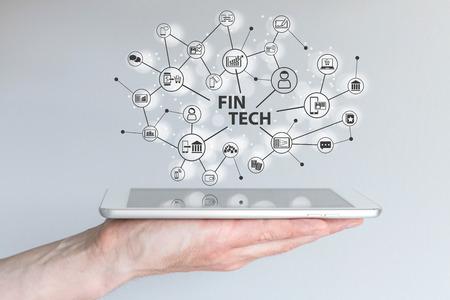 Fin Tech und Mobile Computing-Konzept. Hand hält Tablette vor grauem Hintergrund mit Connected Finanzen, Vertrieb, Marketing und Zahlungsinformationen.