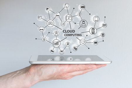 Cloud computing and mobile computing concept. Hand holding tablet or smart phone. Cloud Network of connected devices and information.