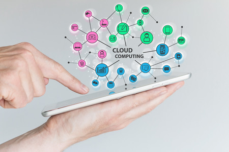 comprised: Cloud computing and mobile computing concept. Hand holding tablet or smart phone. Cloud Services Comprised of various connected devices and objects.