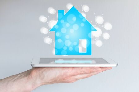 Mobile and online real estate and property sales with smart phone and tablet. Hand holding smart phone or tablet