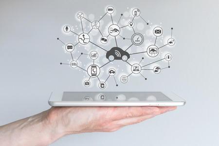 Connected Concept Car. Une main tenant appareil mobile moderne.