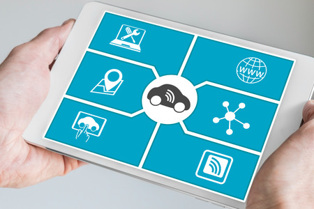 Connected Car and Digital Mobility concept. Hand holding modern tablet. Stock Photo